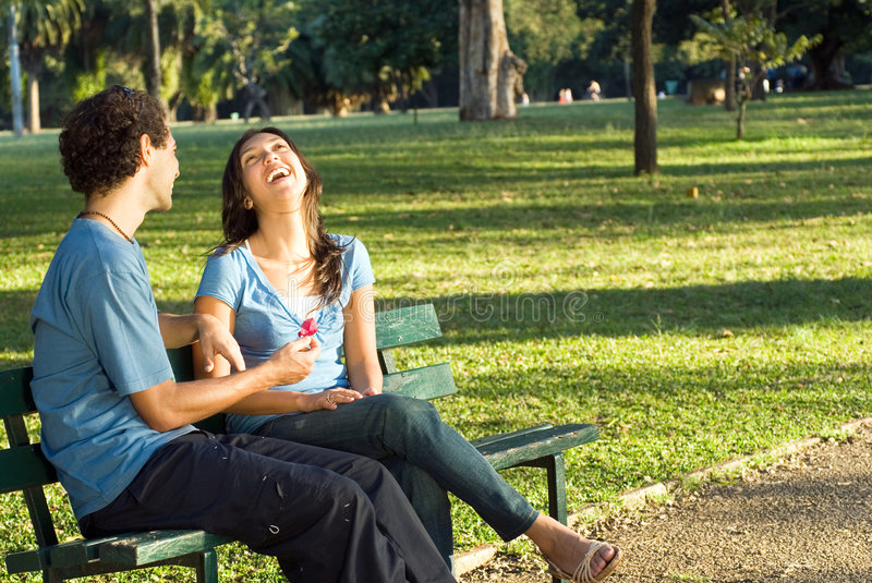 Couple Laughing on a Park Bench - Horizontal stock photo