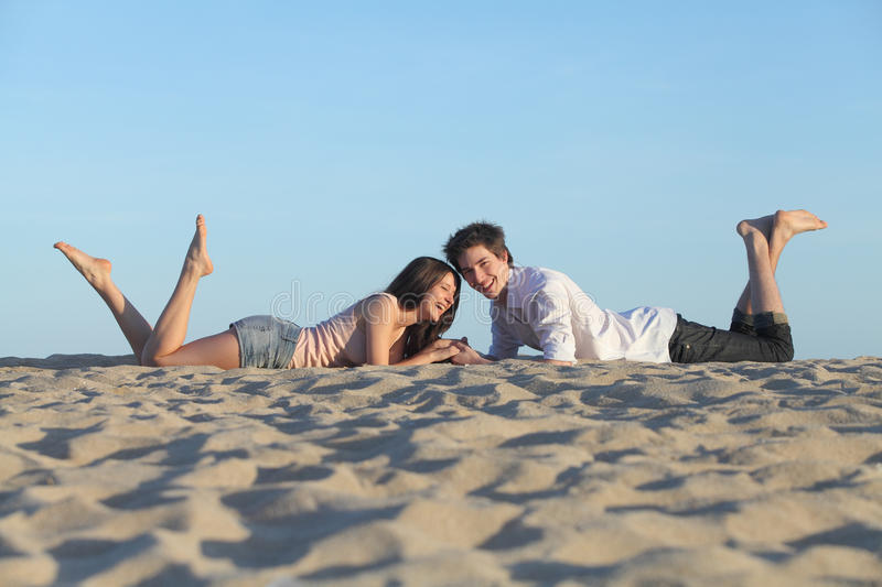 Couple laughing resting on the beach stock image
