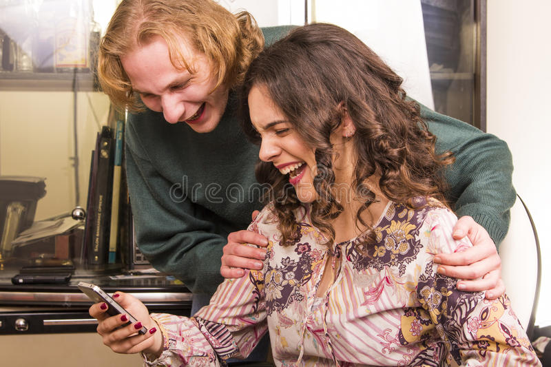 Couple laughing to a message royalty free stock photography
