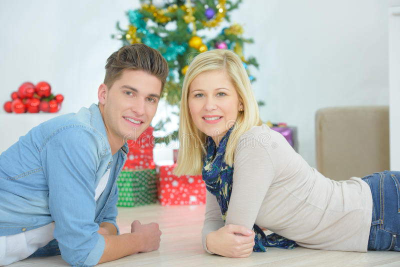 Couple layed in front Christmas tree stock photo