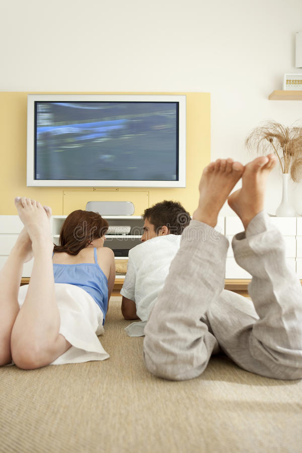 Download Couple Laying Down On Floor Watching TV Stock Photo - Image: 24787166