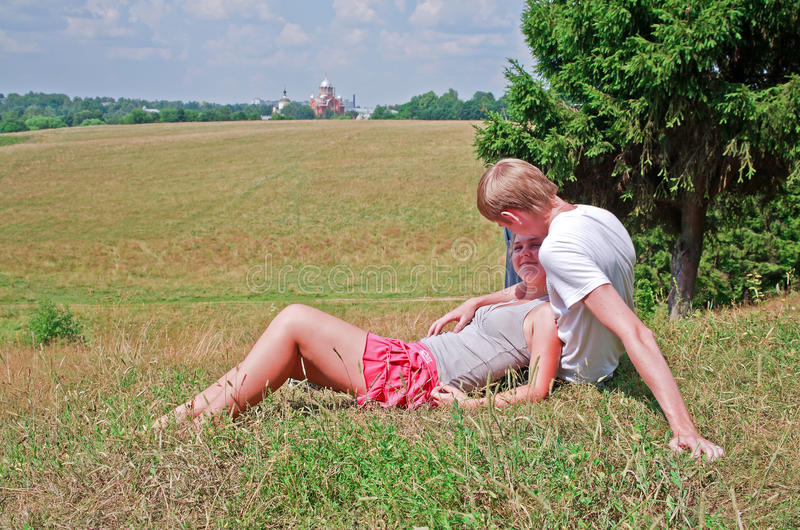 Couple laying on grass near meadow royalty free stock photo