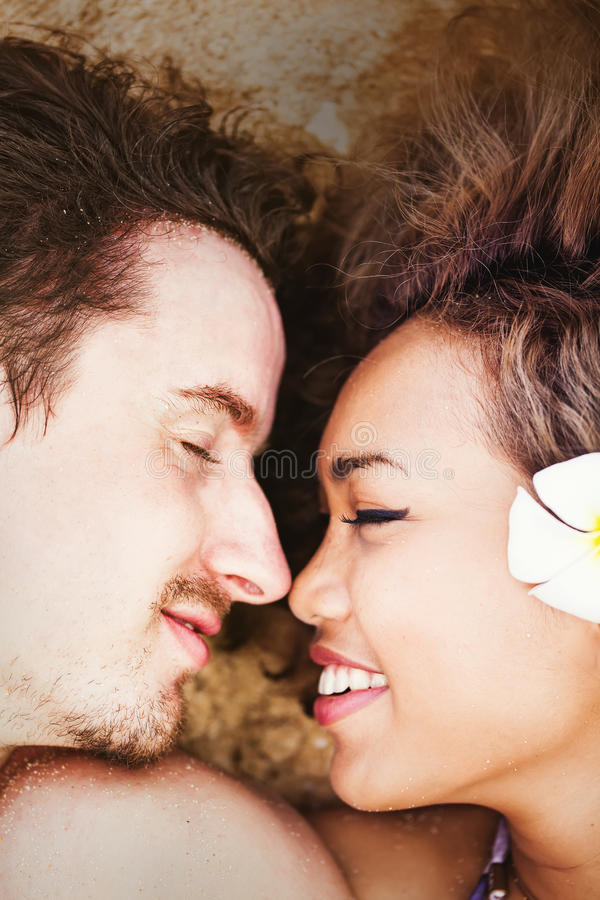 Couple laying and kissing on a beach stock images