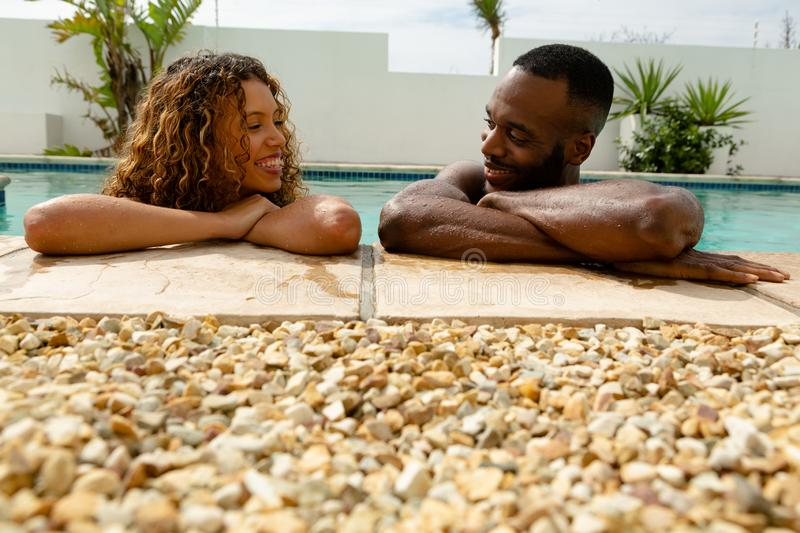 Couple leaning on the edge of a swimming pool and looking each other. Front view of African-american happy young couple leaning on the edge of a swimming pool royalty free stock image