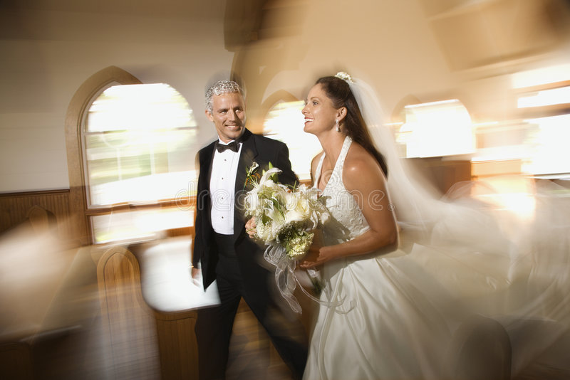 Couple leaving church. Bride and groom leaving church with motion blur effect