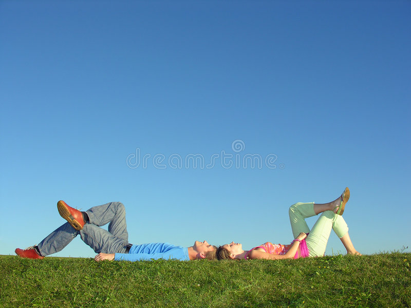 Couple lie on blue sky. And green grass