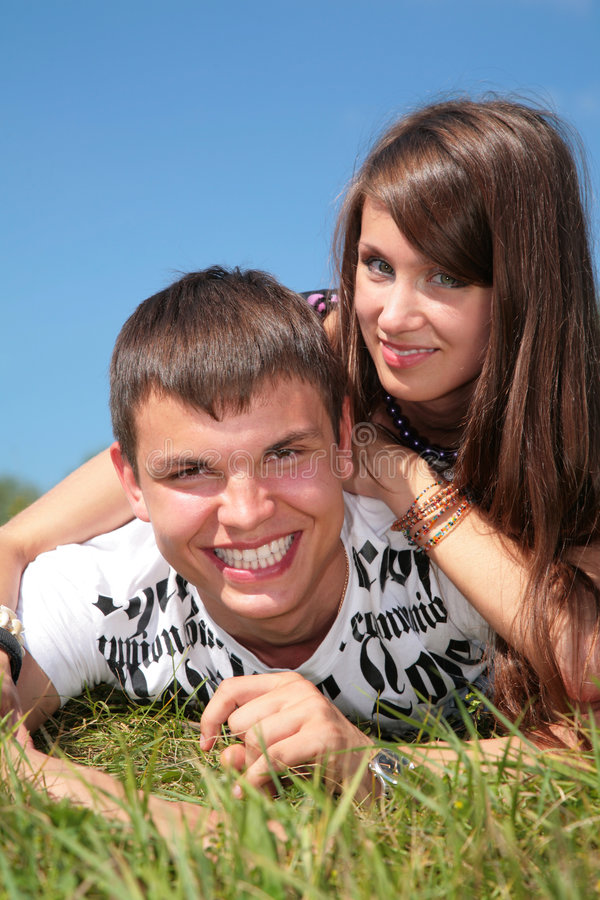 Couple lies on grass stock images