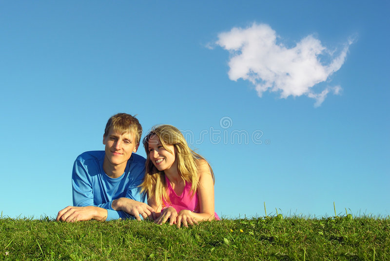 Couple lies on meadow with cloud stock photo