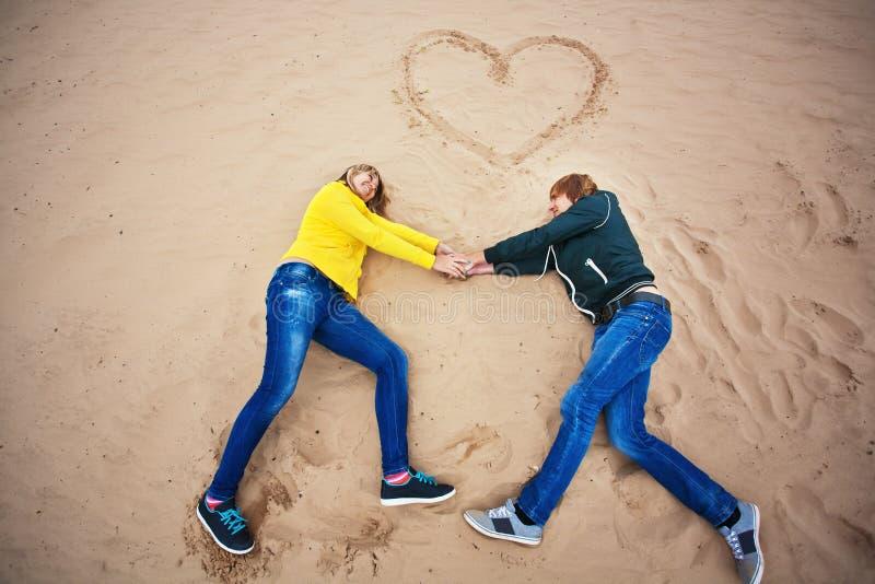 Couple ligger på sanden med en hjärta arkivbilder