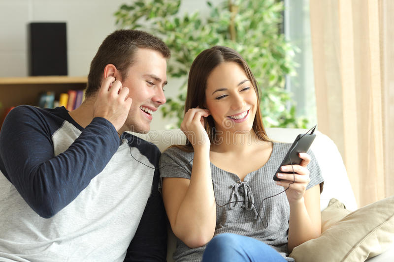 Couple listening music and sharing earphones stock photo