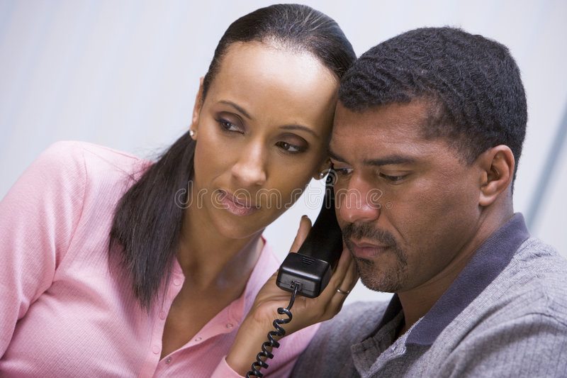 Couple listening to news over phone royalty free stock photo
