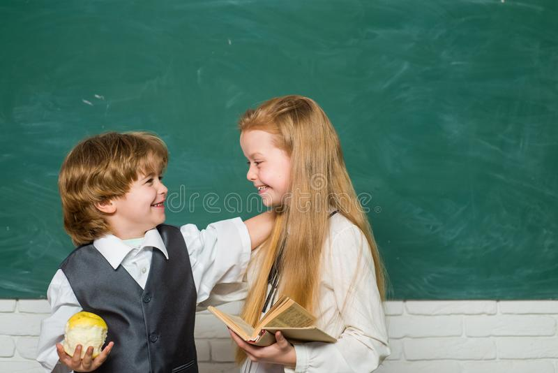 Couple of little girl and boy in classroom. Back to school. Cheerful smiling child at the blackboard. Education. Teacher stock photos