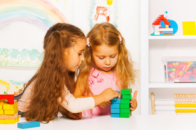 Couple little girls playing stacking wooden blocks. Two girls stacking blocks playing together on the table in kids room stock images