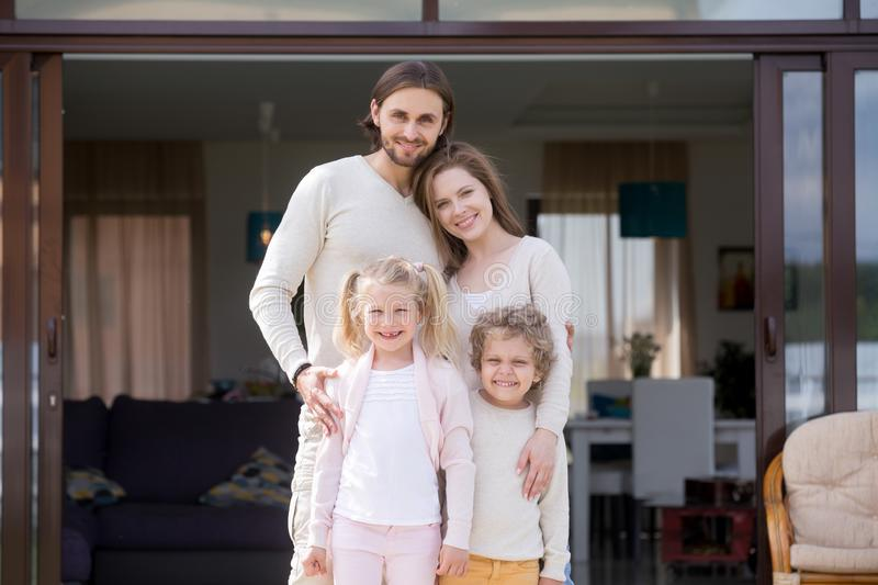 Family with children standing on terrace of new house stock photography