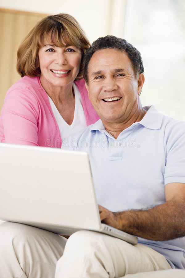 Couple In Living Room With Laptop Smiling Royalty Free Stock Photo