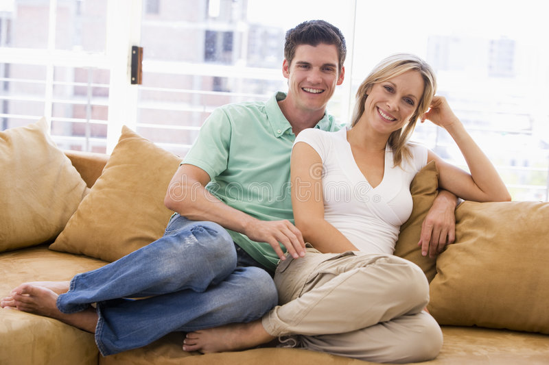 Couple in living room smiling stock photo