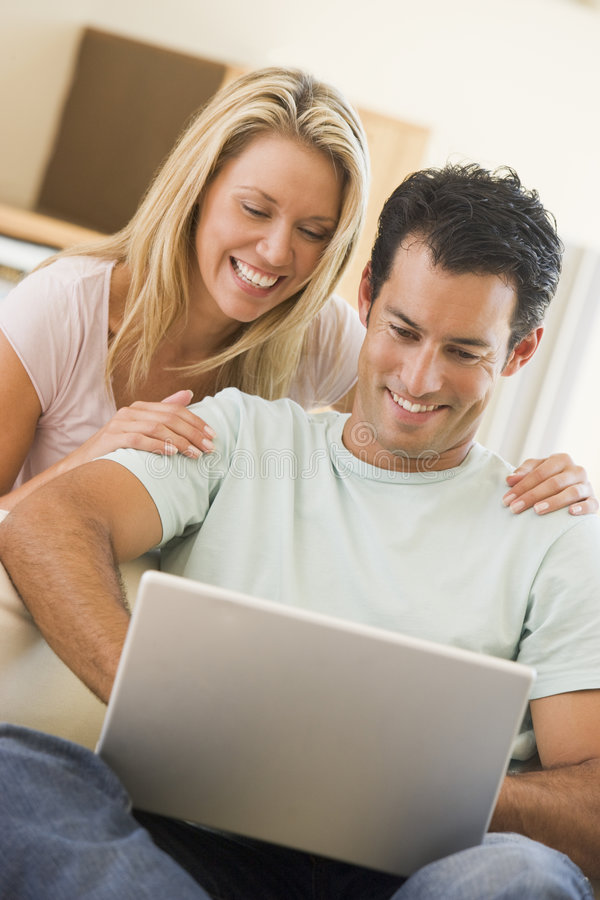 Download Couple In Living Room Using Laptop Smiling Stock Photo - Image: 5927600