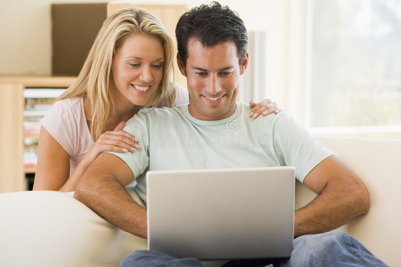 Download Couple In Living Room Using Laptop Smiling Royalty Free Stock Images - Image: 5927609