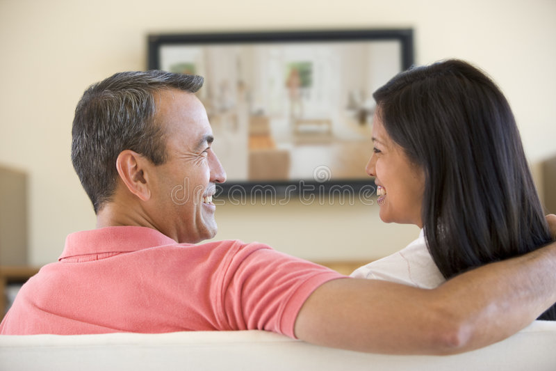 Couple in living room watching television. Smiling stock photos