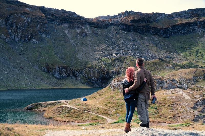 Couple look to distance on mountain top, Balea Lac lake. Space for text, hiking travel tent camping vacation. Transfagarasan. Romania stock images
