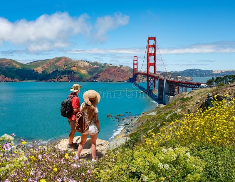 Couple looking at beautiful summer coastal landscape, on hiking trip. Friends relaxing on mountain. Golden Gate Bridge, over Pacific Ocean and San Francisco stock image