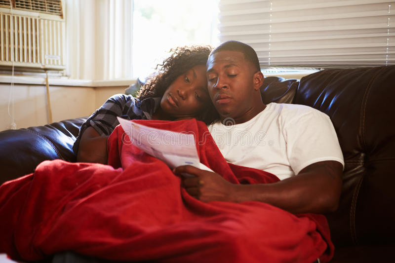 Couple Looking At Bills Keeping Warm Under Blanket At Home stock image
