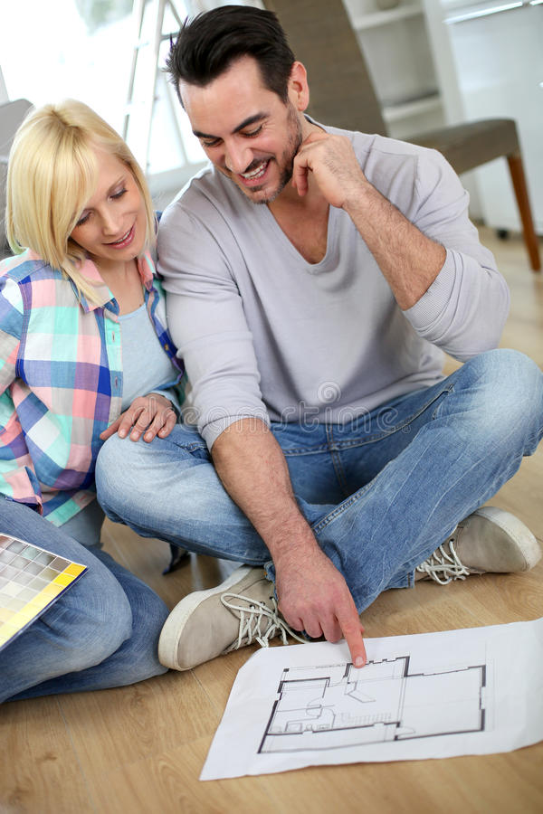 Couple looking blueprint before choosing colors stock photo