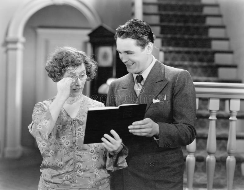 Couple looking at a book together. (All persons depicted are no longer living and no estate exists. Supplier grants that there will be no model release issues royalty free stock photography