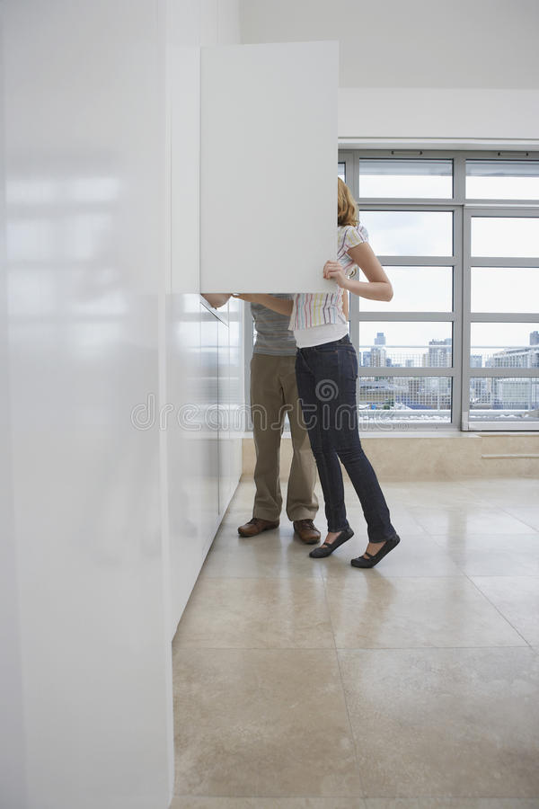 Couple Looking In Cupboard In Empty Apartment stock images