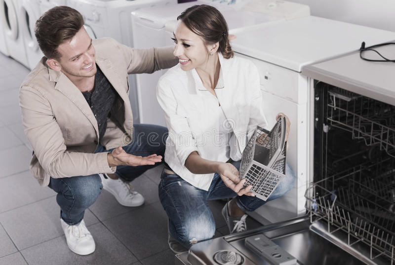 Couple looking at dishwashers in domestic appliances shop royalty free stock images