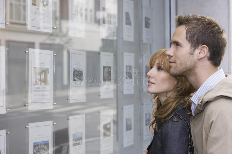 Couple Looking At Display At Real Estate Office. Side view of a young couple looking at window display at real estate office stock images