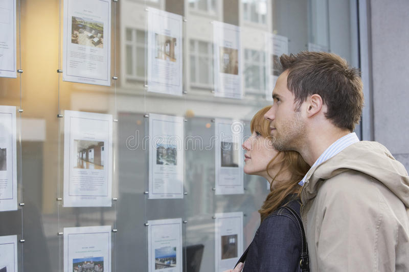 Couple Looking At Display At Real Estate Office. Side view of a young couple looking at window display at real estate office royalty free stock images