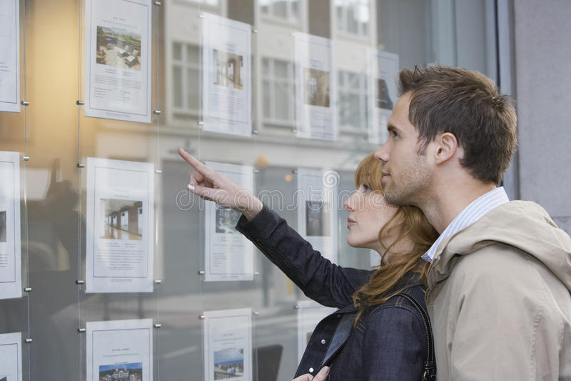 Couple Looking At Display At Real Estate Office. Side view of a young couple looking at window display at real estate office royalty free stock photo