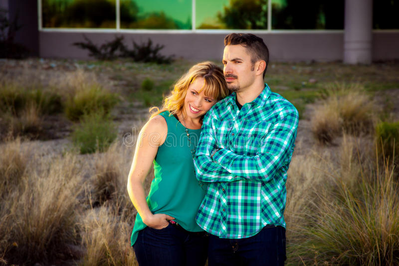 Couple Looking into the Distance. A women leans on her husband as they look off camera. She has a beautiful and content smile as he stands firm and confident royalty free stock image