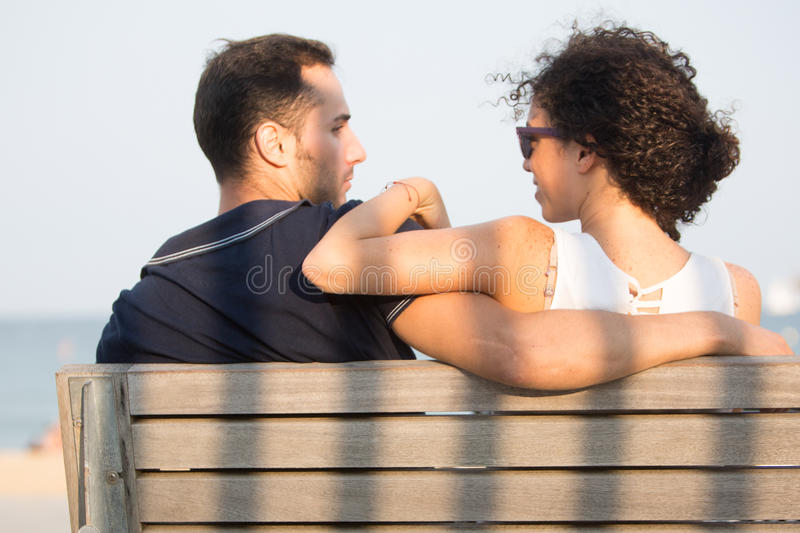 Couple looking each other in the eyes. Couple sitting on bench during sunset with shadows stock photography