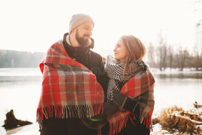 Couple looking each other near winter lake under plaid stock photo