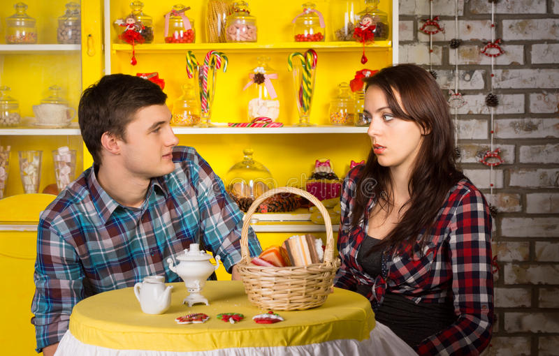 Couple Looking Each Other at the Snack Bar. Young White Couple in Checkered Shirts Looking Each Other at the Snack Bar While Having a Date royalty free stock images