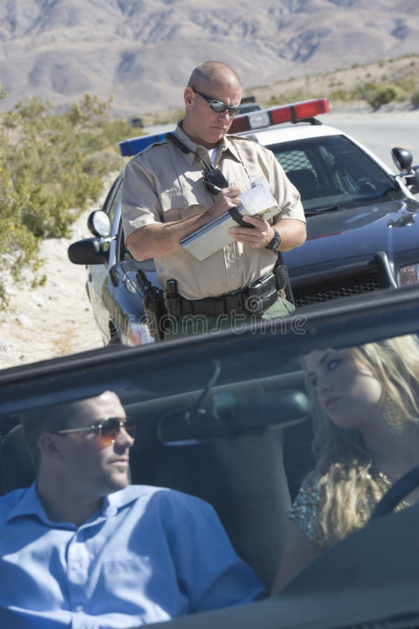 Couple Looking At Each Other With Traffic Cop Writing Ticket Royalty Free Stock Photography