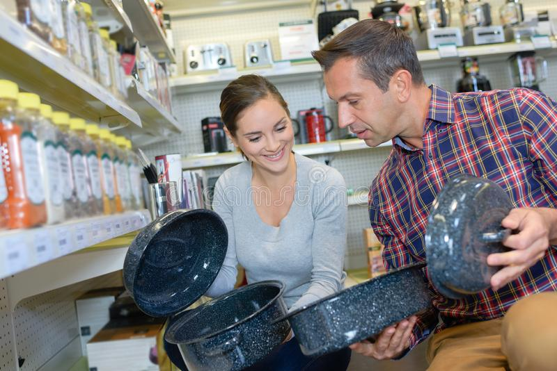 Couple looking at enamel cooking dishes royalty free stock images