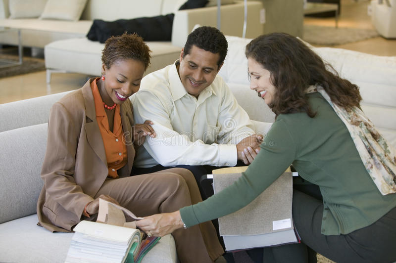 Couple Looking at fabric Swatches With Saleswoman in furniture store royalty free stock photography