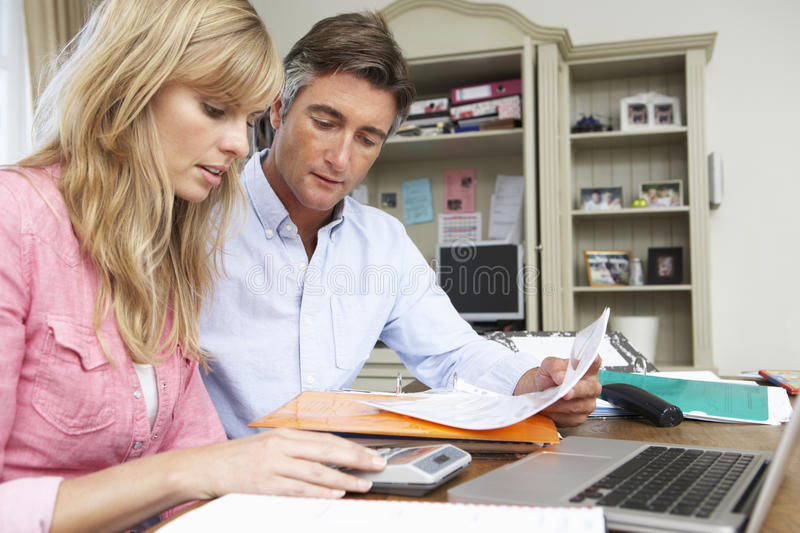 Couple Looking At Finances In Home Office Together royalty free stock images