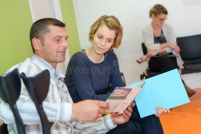 Couple looking at leaflet in medical waiting room. Medical stock photos