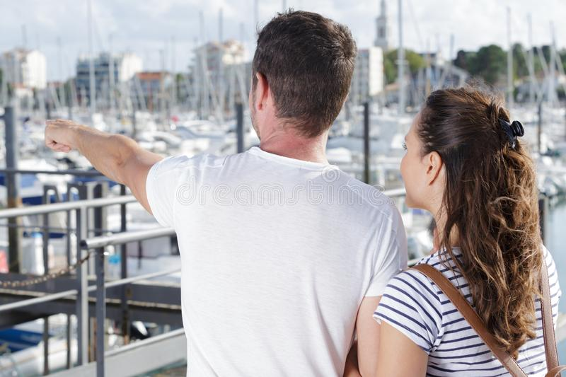 Couple looking out over port man pointing into distance royalty free stock photography
