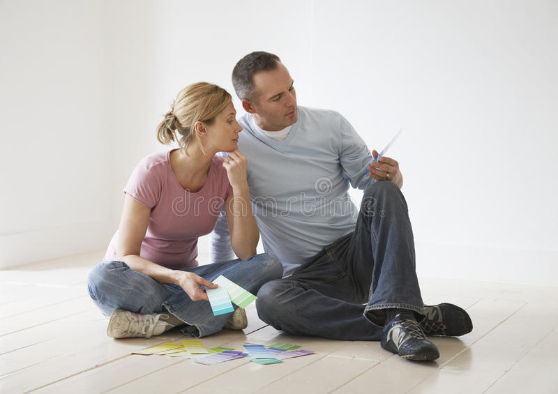 Couple Looking At Paint Swatches On Floor. Couple sitting on floor and looking at paint swatches stock photo
