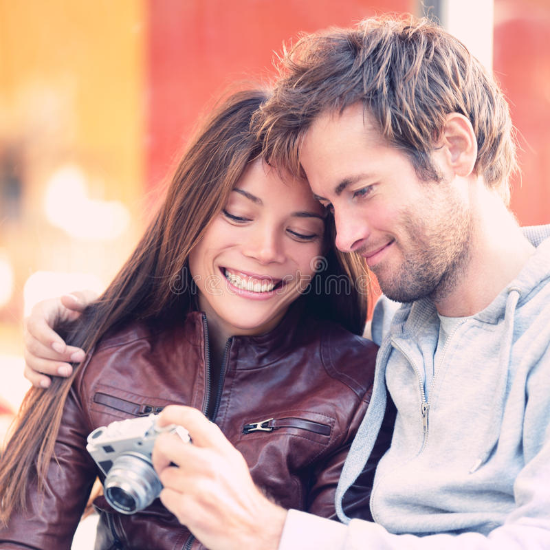 Couple looking at pictures on camera. Beautiful young lovers having fun together outside looking at photos on vintage retro camera. Interracial couple, Asian stock photography