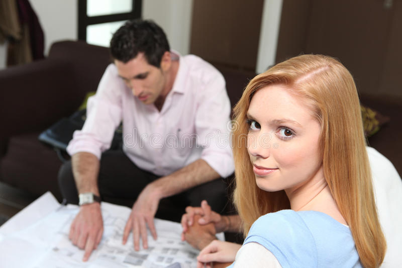 Couple looking at plans. Woman and men looking at real estate plans stock image