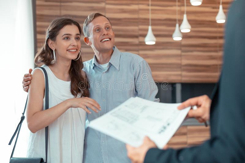 Couple looking at realtor giving them the documents royalty free stock images