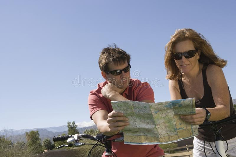 Couple Looking At Roadmap. Caucasian couple looking at roadmap with bicycle stock image