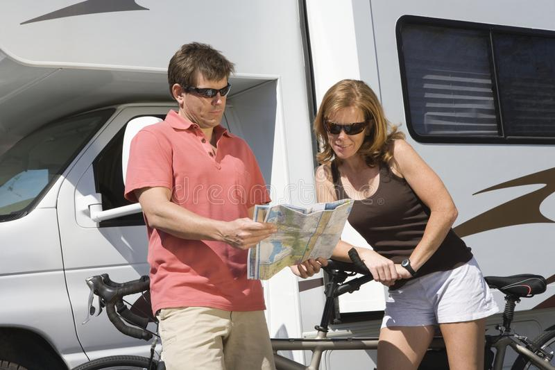 Couple Looking At Roadmap Standing Against RV. Caucasian couple with bicycles looking at roadmap standing against recreational vehicle royalty free stock photos