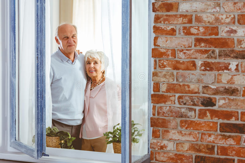Couple looking at the sky. Elder couple looking through the open window at the sky together stock images